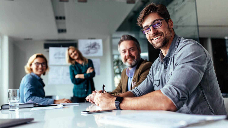 Bemanning møterom mann med briller smiler til kamera