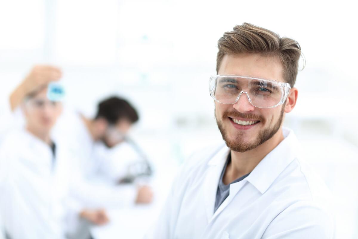 Laboratorie assistent med beskyttelses briller smiler til kamera